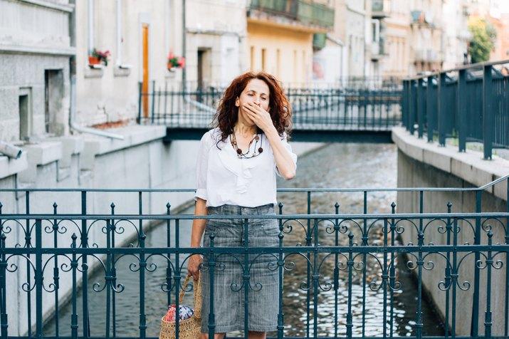 Tired woman yawning on a bridge