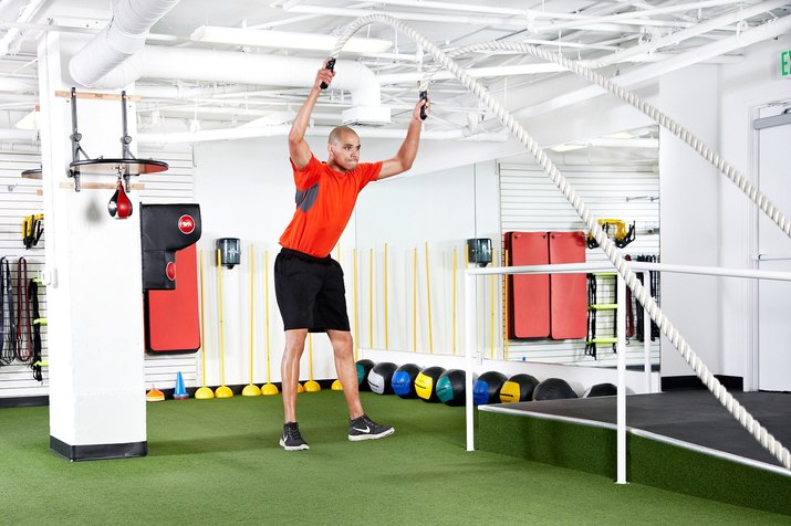 Man doing jump squats to power slams with the battle ropes