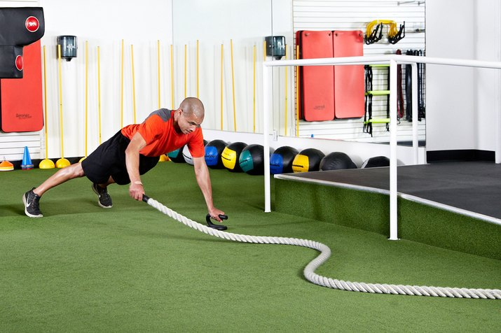 Man doing planks with single-arm snake with the battle ropes