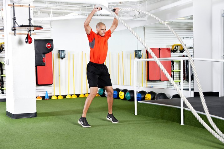 Man doing underhand power jacks with the battle ropes