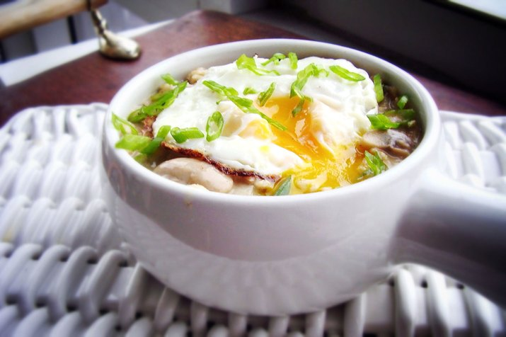 A bowl of oatmeal with herbs, mushrooms and egg