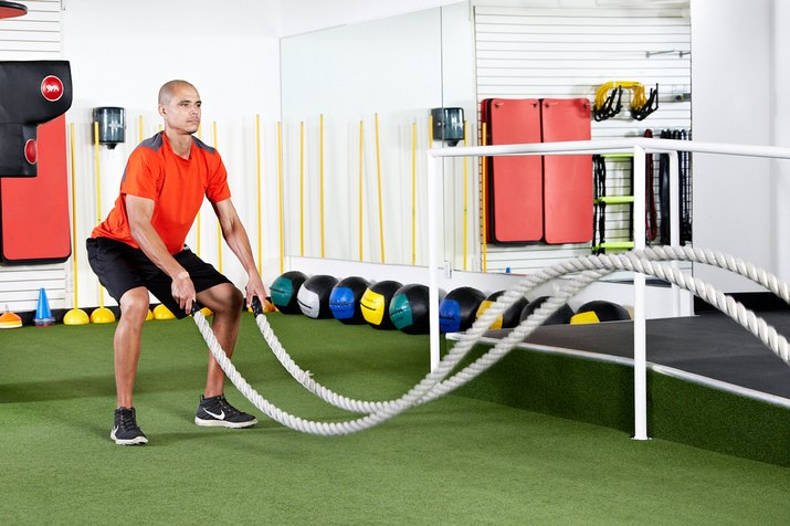Man doing standing squats with double waves with the battle ropes