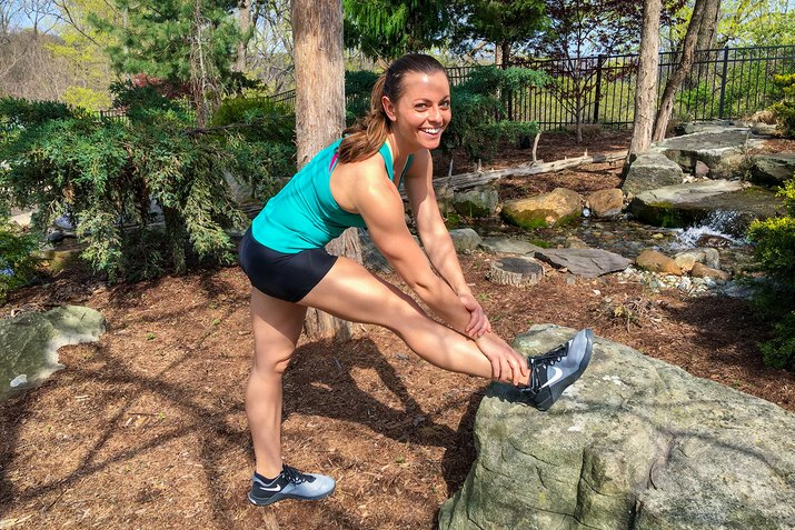 woman stretching her legs on a rock outside
