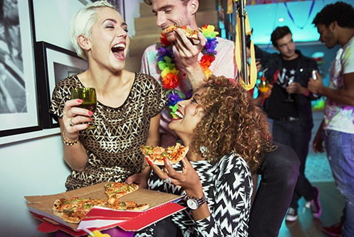 Friends eating pizza at party