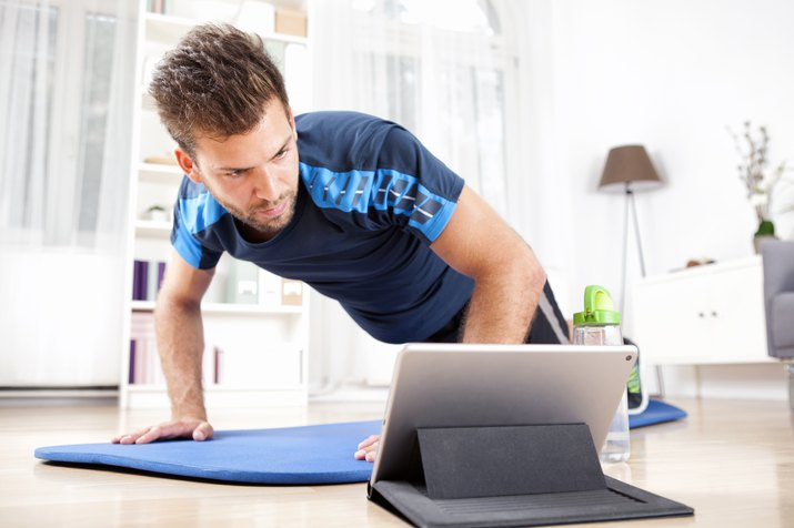 Man doing plank while watching movie on tablet