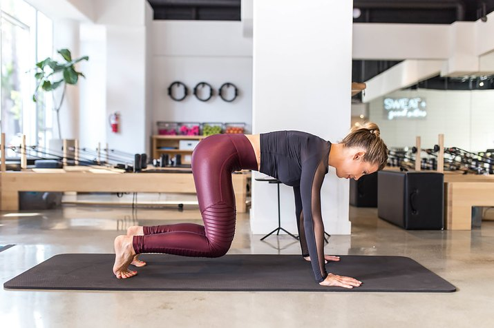 woman doing Knees Off Hold on a mat in a Pilates studio