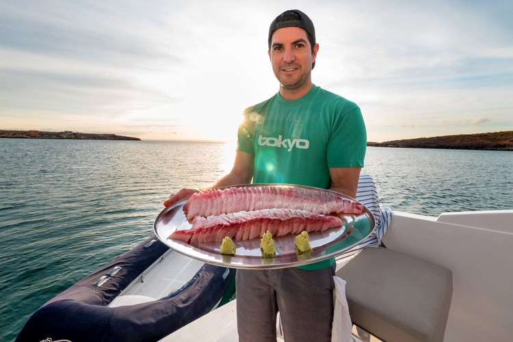 Omega Blue co-founder and executive chef  Cody Requejo with a platter of Baja Kanpachi sashimi.