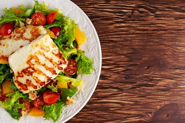 Grilled Halloumi Cheese salad with orange, tomatoes and lettuce - vegetarian dish.