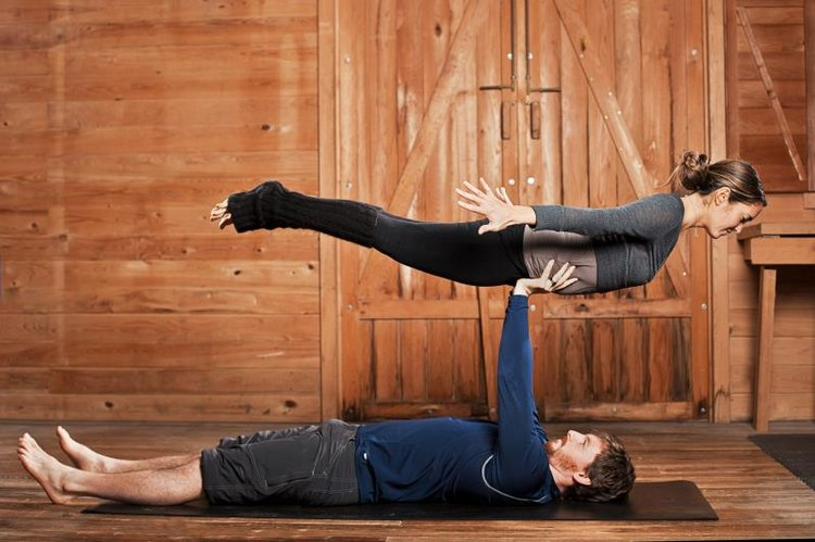 A man and woman balancing Acroyoga or flying yoga