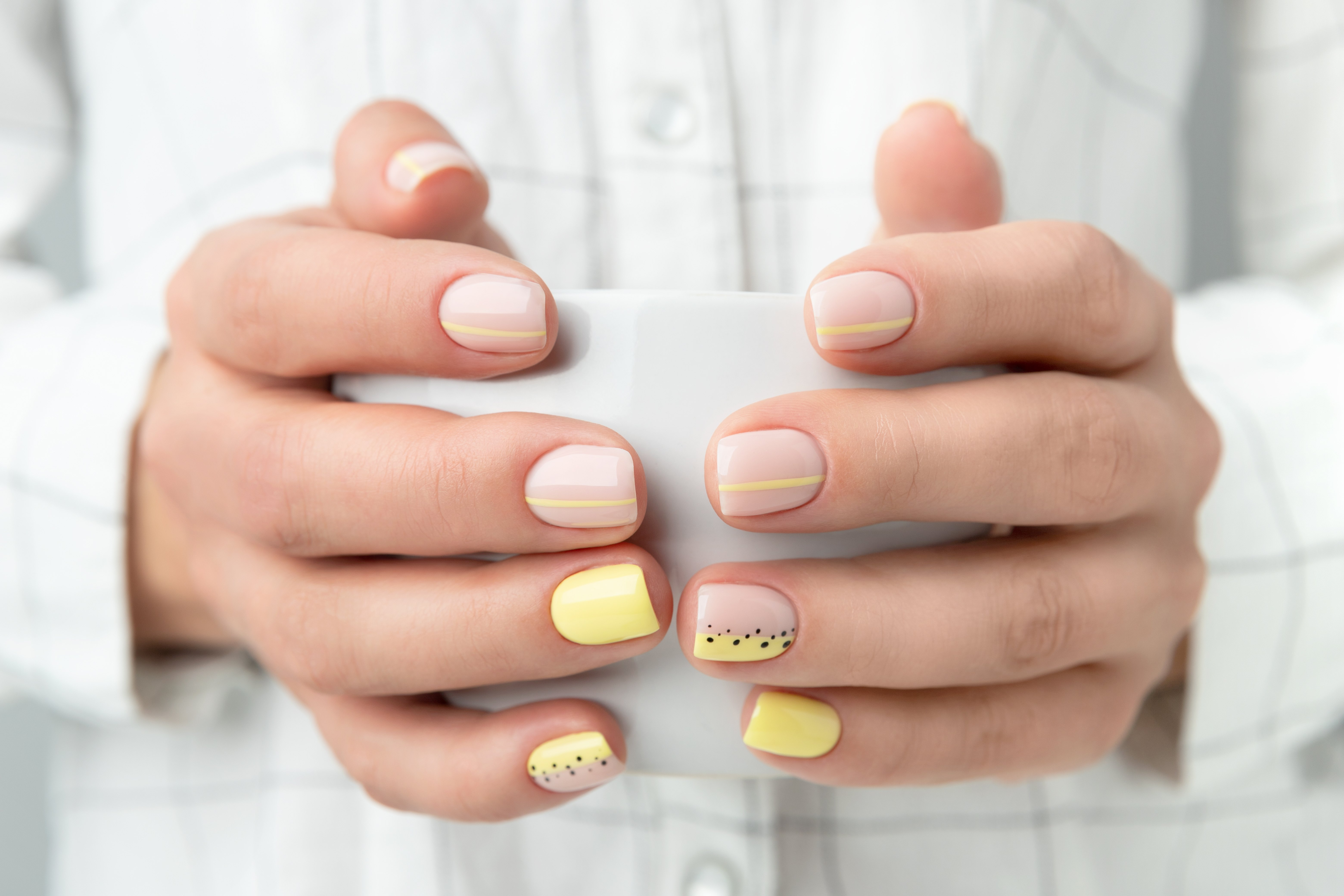close up of hands with painted nails holding mug