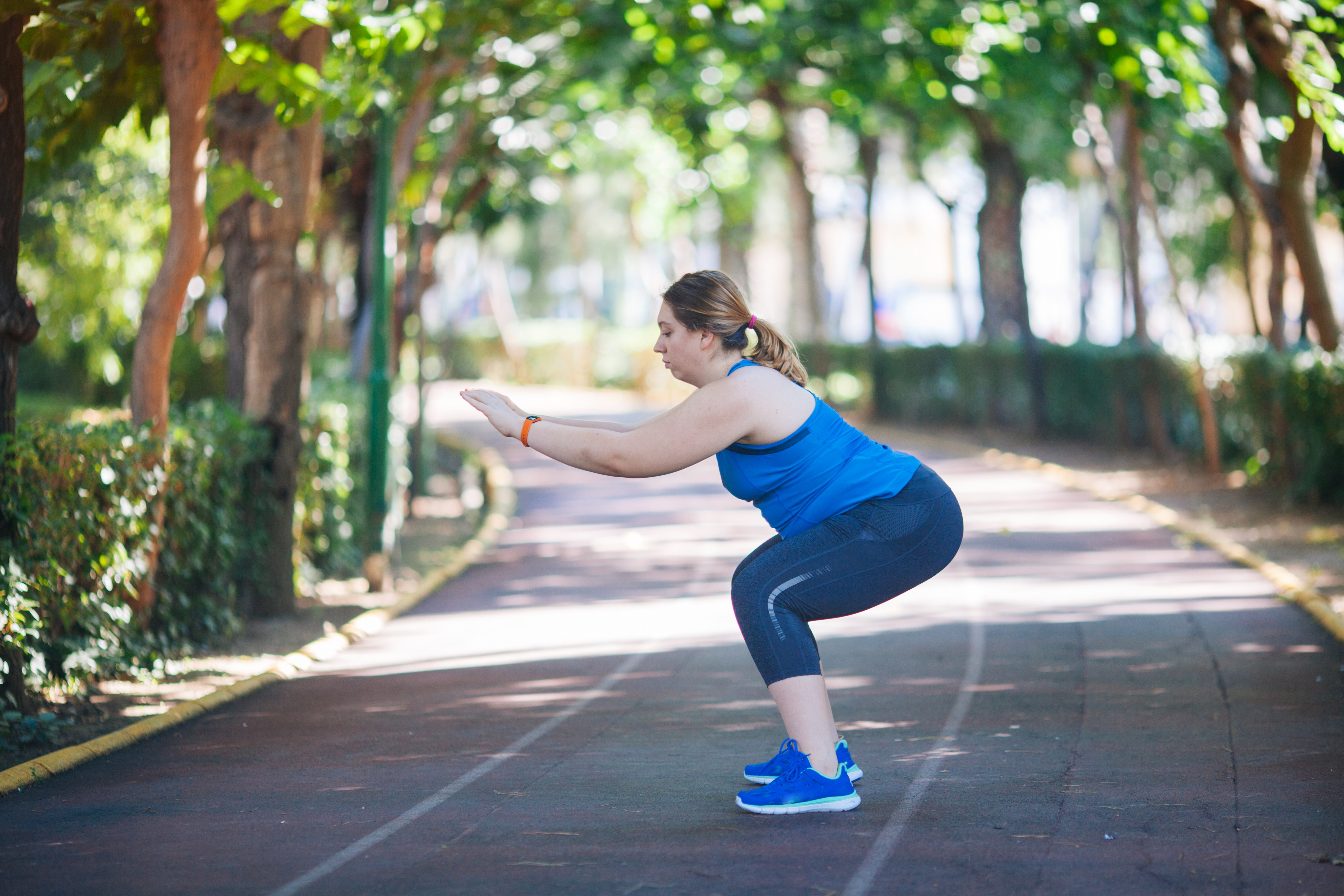 woman doing squat workout outside
