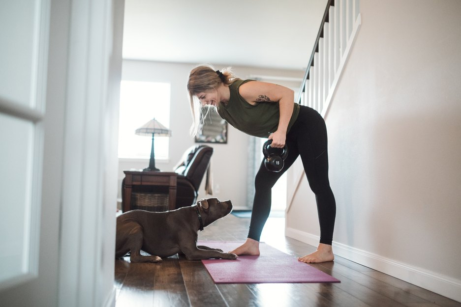 woman strength training with a kettlebell at home with her dog