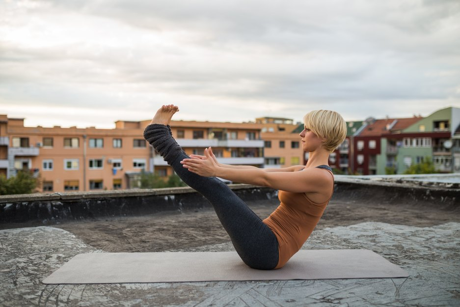 Woman Doing Yoga-Boat Pose/Navasana on a Rooftop