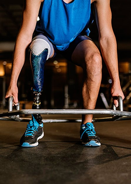 close up of person with amputated leg lifting weights in inclusive gym