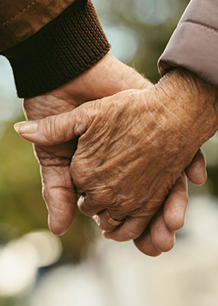 close up of older adults holding hands