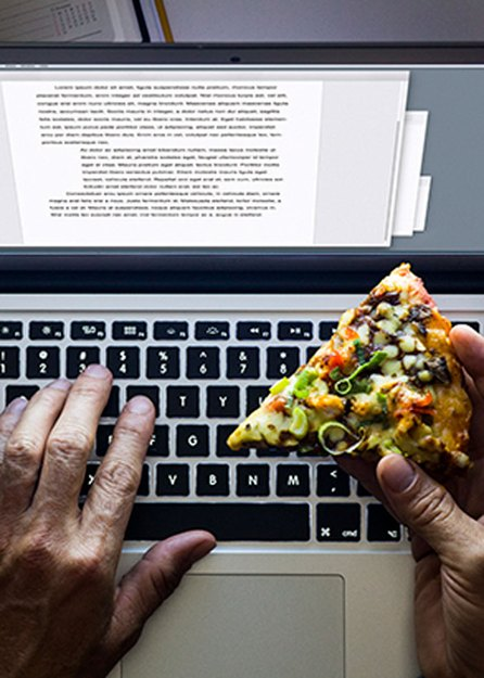 hands typing on keyboard late at night holding pizza