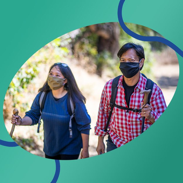 couple hiking wearing face masks to take more steps