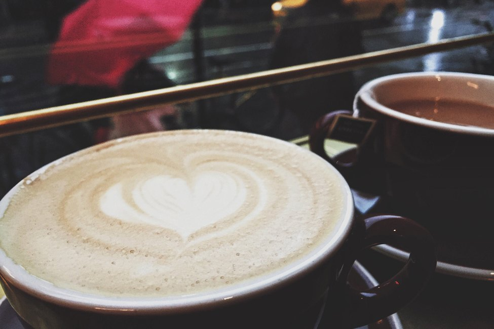 Latte with heart in the foam on a rainy day.